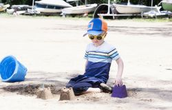 Toddler with Hat & Sunglasses Plays on a Sandy Beach Building Sand Castles stock photography