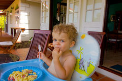 A toddler having breakfast outdoors Royalty Free Stock Photo