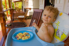 A toddler having breakfast outdoors Royalty Free Stock Images