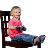 Toddler having fun sitting painting herself Royalty Free Stock Image