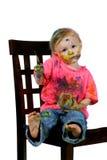 Toddler having fun sitting painting herself Royalty Free Stock Images