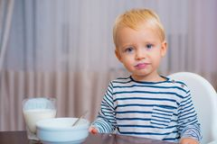 Toddler having snack at home. Boy cute baby eating breakfast. Child eat porridge. Kid cute boy blue eyes sit at table stock photo
