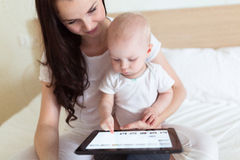 Toddler with her mother playing on the bed in the tablet, Royalty Free Stock Photography