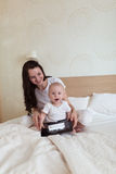 Toddler with her mother playing on the bed in the tablet, Royalty Free Stock Image