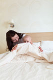 Toddler with her mother playing on the bed in the tablet, Royalty Free Stock Images
