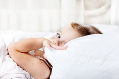Toddler hiding behind  pillow Stock Images