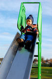 Toddler high up on the slide. Toddler sitting on top of the slide Royalty Free Stock Photo