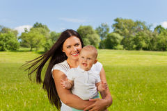 Toddler and his mummy carrying him in meadow Royalty Free Stock Photography