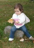 Toddler holding a big leaf she found. Little girl holding a big leaf she found as she discovers autumn leaves while sitting on a rock Royalty Free Stock Photography