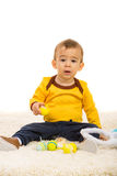 Toddler holding Easter eggs. Toddler boy holding Easter eggs with chick and sitting on fur carpet Stock Photography
