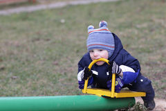Toddler holding handle of seesaw by teeth Stock Photo