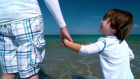 Toddler holding hands with his father at the sea shore