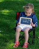 Toddler holding a sign saying Daddy I love you Royalty Free Stock Photography