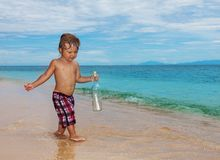 Toddler holding sos bottle. Toddler found sos bottle walking on the beach Royalty Free Stock Photos
