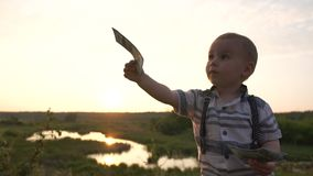 A toddler holds a stack of dollars and gives them to adult one by one bill. He is wearing a stylish shirt. Action in sunny summer evening in slow motion stock footage