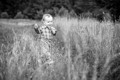 Toddler in a huge meadow. Black and white natural emotions portrait stock photography