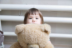 Toddler hugging teddy bear indoor in her room, little child hiding behind the toy Royalty Free Stock Photos