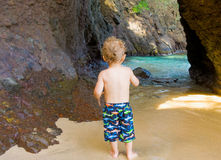 A toddler inspecting a cave at a beach in the caribbean Royalty Free Stock Images