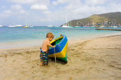A toddler inspecting a wooden double-ender made on bequia Stock Images