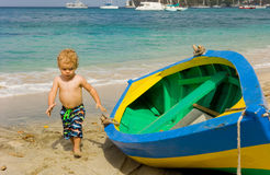 A toddler inspecting a wooden double-ender made on bequia Royalty Free Stock Photo