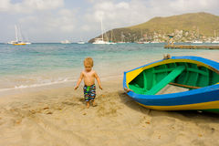 A toddler inspecting a wooden double-ender made on bequia Royalty Free Stock Images