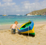 A toddler inspecting a wooden double-ender made on bequia Stock Photo
