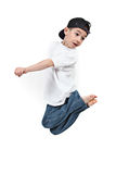 Toddler jumping midair. Young barefoot preschool child with casual clothes jumping midair; white studio background royalty free stock image