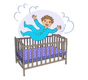 Toddler jumps in the bed stock images