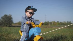 Toddler kid in funny glasses biking. Helping to ride a bike. Learning to ride a bike concept. Toddler kid in funny glasses biking. Helping to ride a bike stock video