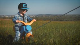 Toddler kid in funny glasses biking. Helping to ride a bike. Learning to ride a bike concept. Toddler kid in funny glasses biking. Helping to ride a bike stock video footage