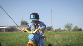 Toddler kid in funny glasses biking. Helping to ride a bike. Learning to ride a bike concept. Toddler kid in funny glasses biking. Helping to ride a bike stock footage