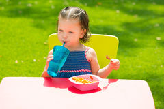 Toddler kid girl drinking eating pasta in garden Stock Photo