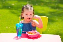 Toddler kid girl eating macaroni tomato pasta Stock Image
