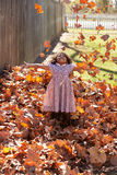 Toddler kid girl playing with autumn leaves Stock Image