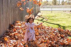 Toddler kid girl playing with autumn leaves Royalty Free Stock Photo