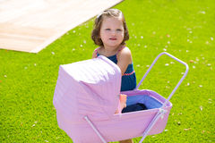 Toddler kid girl playing with baby cart in green turf Royalty Free Stock Photography