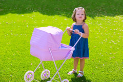 Toddler kid girl playing with baby cart in green turf Royalty Free Stock Photo