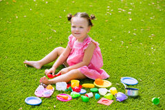 Toddler kid girl playing with food toys sitting in turf Stock Images