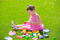 Toddler kid girl playing with food toys sitting in turf Stock Image
