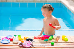 Toddler kid girl playing food toys in swimming pool Stock Images