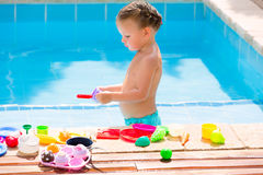 Toddler kid girl playing food toys in swimming pool Royalty Free Stock Photos