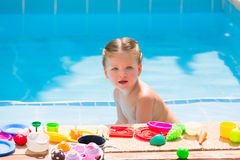 Toddler kid girl playing food toys in swimming pool Royalty Free Stock Image