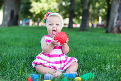 Toddler kid girl playing wooden cubes in green turf grass garden Stock Images