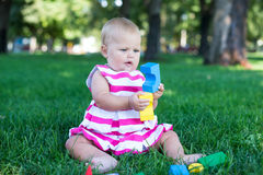 Toddler kid girl playing wooden cubes in green turf grass garden Stock Photo