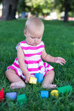 Toddler kid girl playing wooden cubes in green turf grass garden Royalty Free Stock Images