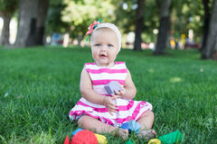 Toddler kid girl playing wooden cubes in green turf grass garden Royalty Free Stock Photo