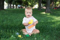 Toddler kid girl playing wooden cubes in green Royalty Free Stock Images