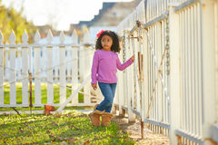 Toddler kid girl portrait in a park fence Stock Photos