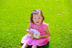Toddler kid girl with white hen in green turf Royalty Free Stock Photo