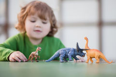 Toddler kid playing with a toy dinosaur Royalty Free Stock Photography